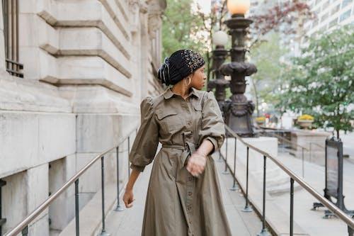 Woman in Brown Coat Walking on White Wooden Bridge