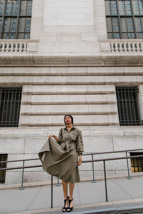 Woman in Brown Coat Standing Near White Concrete Building