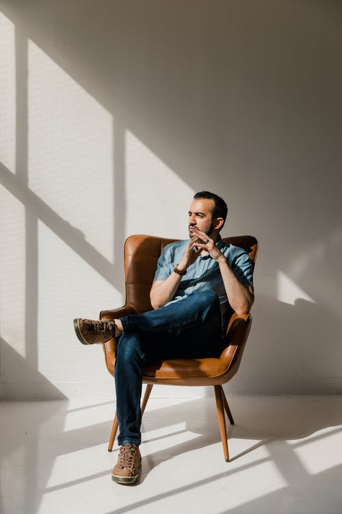Man in Blue Polo Shirt Sitting on Brown Wooden Chair