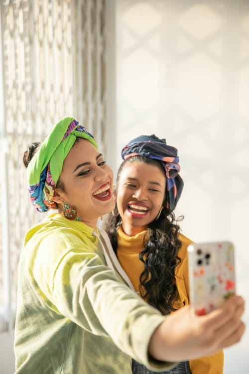 Smiling Woman in Yellow Shirt Beside Smiling Girl in Green Jacket