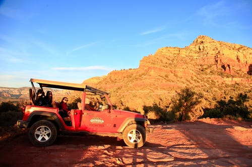 Red All-terrain Vehicle on Brown Rock Field during Sunset