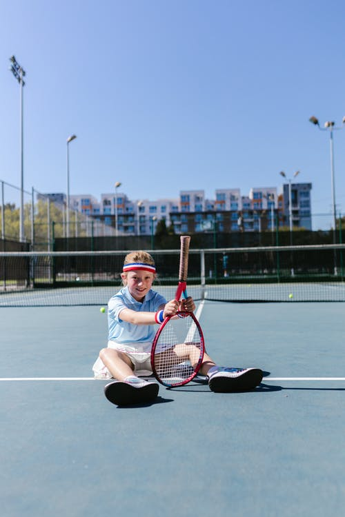 Girl Smiling while Sitting on the Tennis Court