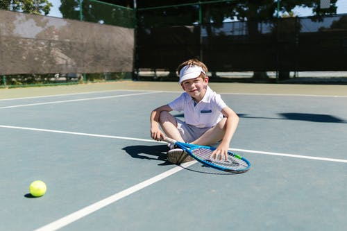 Boy Smiling while Sitting on the Tennis Court