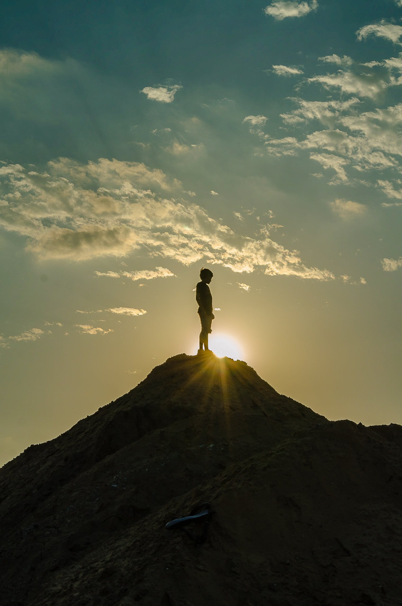 Silhouette of a Man Standing on a Mountain