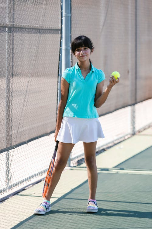 Woman in Blue Tank Top and White Skirt Holding Tennis Racket