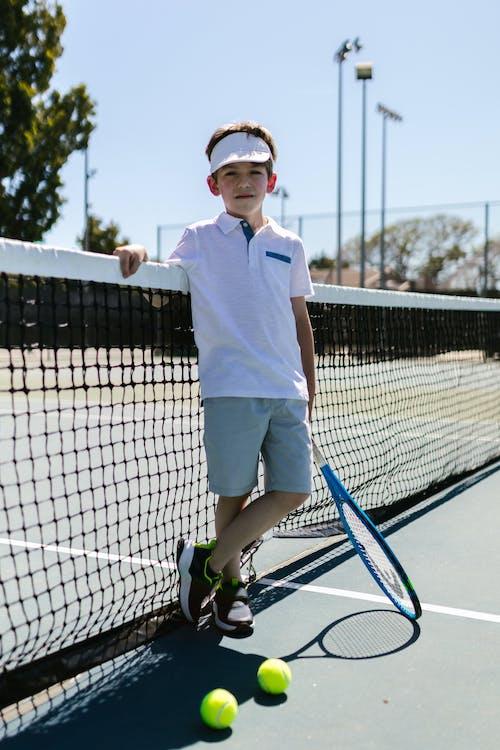 Boy Wearing Sportswear Standing by the Tennis Net