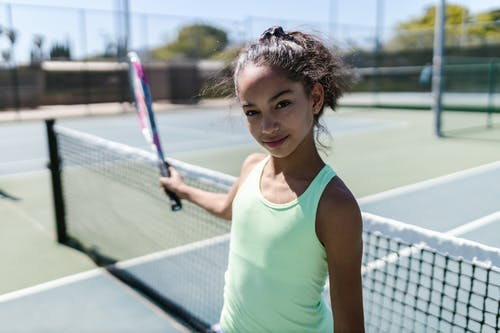 Girl Wearing Sportswear Standing by the Tennis Net