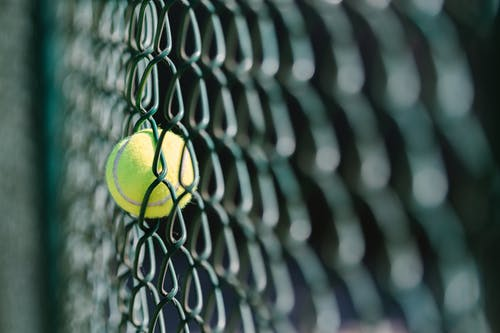 Close-Up View of a Tennis Ball on a Wire Fence