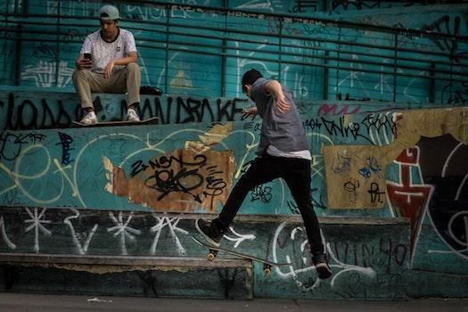 Man Wearing Geay Shirt Playing Skateboard