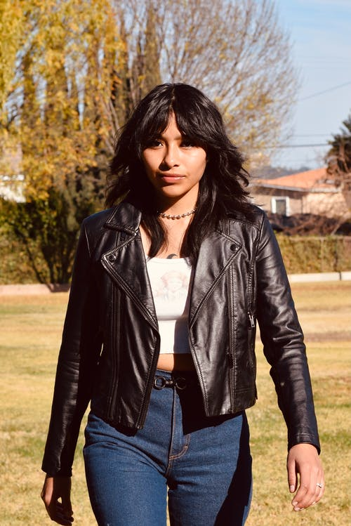 Stylish young ethnic female in leather jacket strolling on meadow while looking away in sunlight