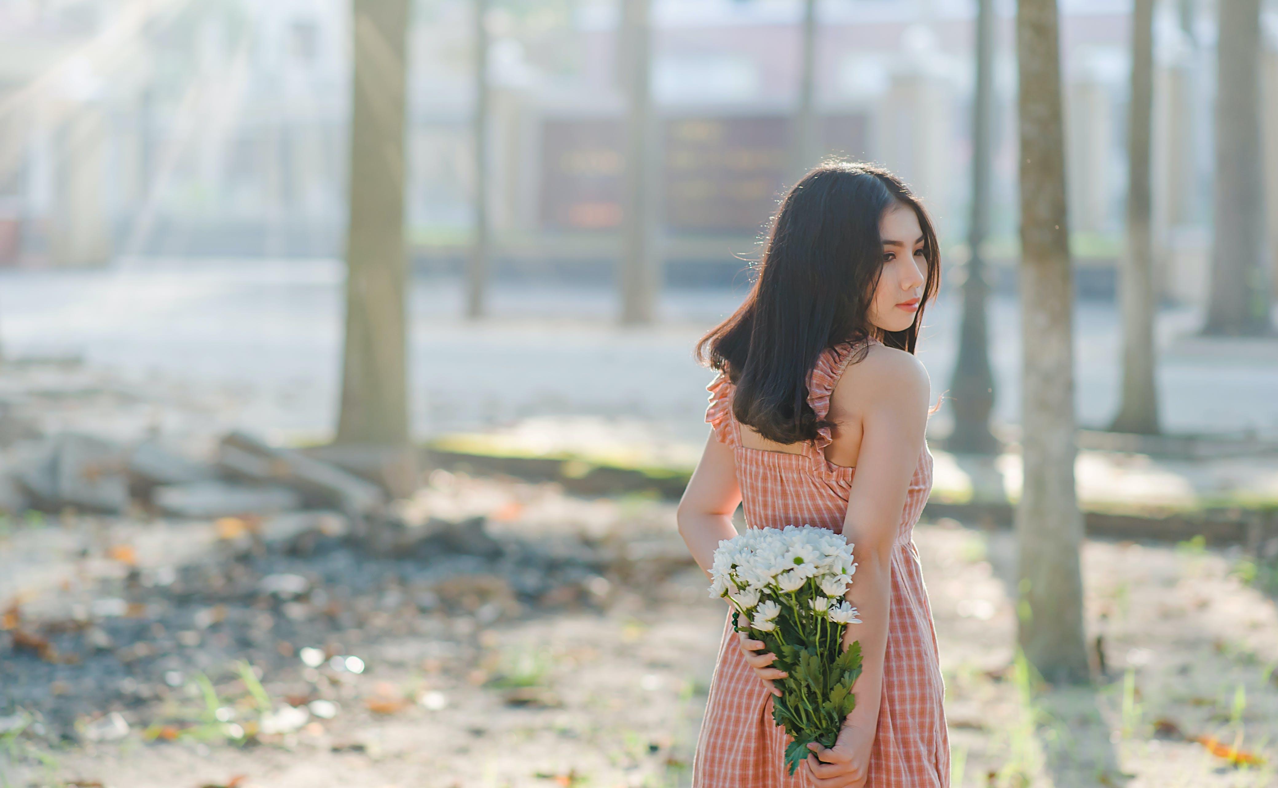 Woman Wearing Orange Sleeveless Dress Holding a Bouquet of Flowers