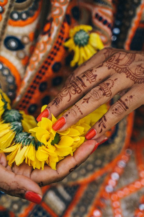 Person With Yellow and Red Flower on Hand