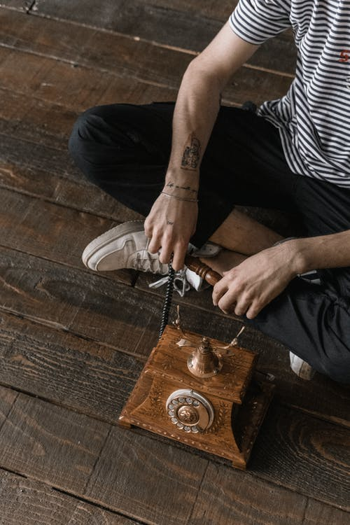 Crop man sitting on wooden floor