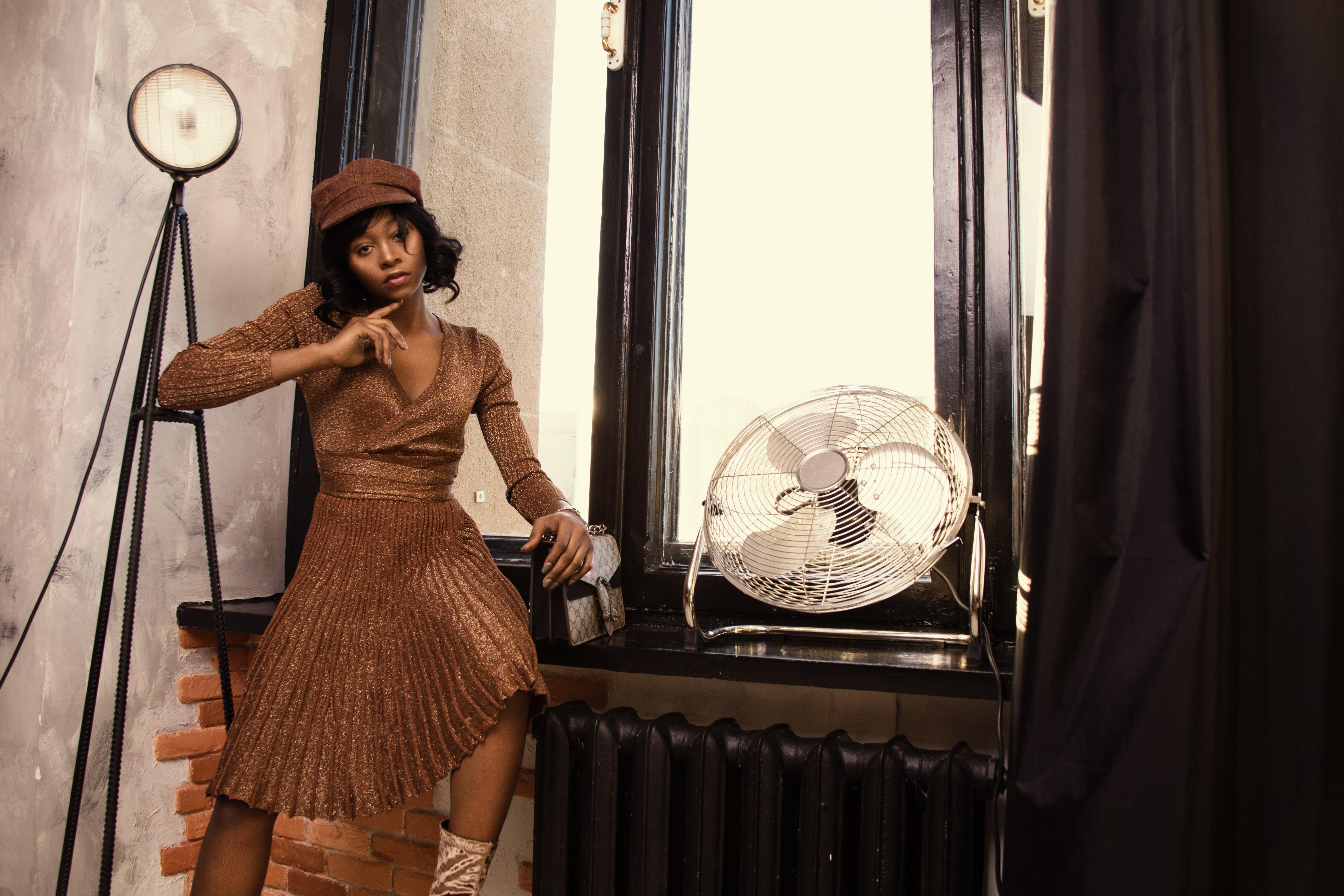 Woman Wearing Brown Dress Near Fan Standing Beside Table at Daytime