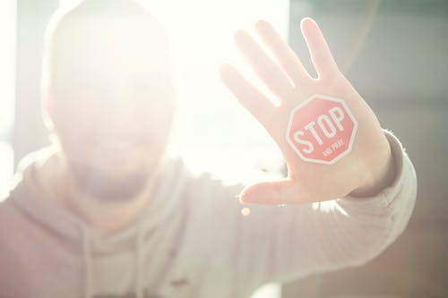 Blurry Photograph of Man Raising Left Hand With Stop Signage Sticker on Palm