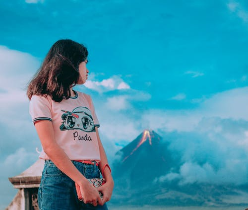 Photography of a Girl In Front of Erupting Volcano