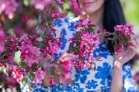 Woman in Blue and White Floral Dress Holding Pink Flowers