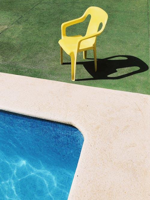 Yellow Plastic Armchair Beside Swimming Pool