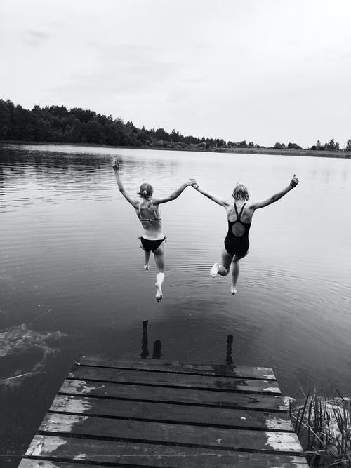 Grayscale Photo of 2 Women Jumping on Water