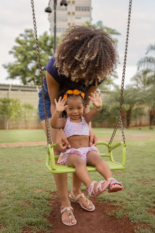 Anonymous mom with Afro hairstyle leaning forward above cheerful ethnic girl while having fun on swing in urban park