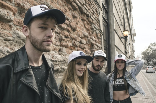 Group of People Wearing Fitted Caps Beside Road