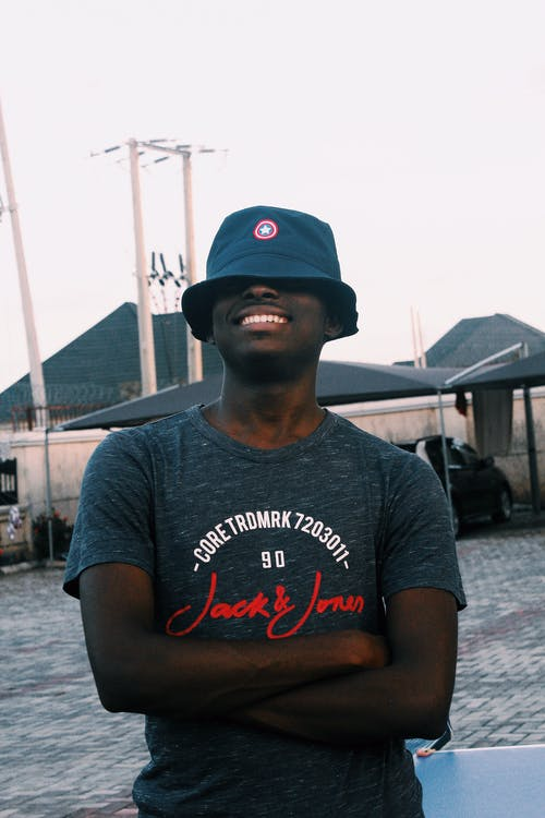 Smiling black man hiding face with hat
