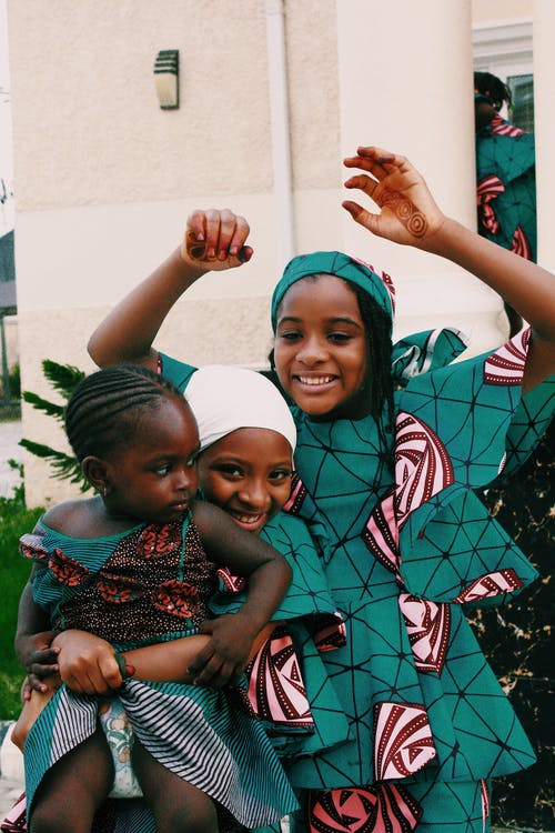 Smiling black sisters in colorful clothes having fun together