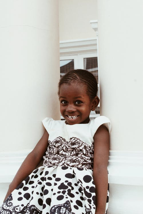 Adorable little African American girl wearing dress smiling brightly while sitting between white columns and looking at camera