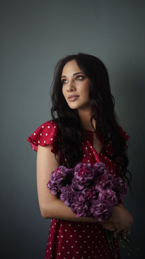 Woman Wearing a Polka Dot Dress Holding a Bouquet of Flowers