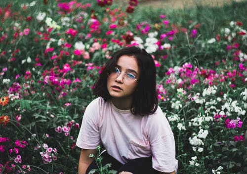 Girl in White T-shirt Surrounded by Flowers