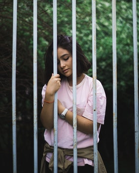 Woman Wearing Pink Crew-neck T-shirt Standing and Leaning Behind White Bars