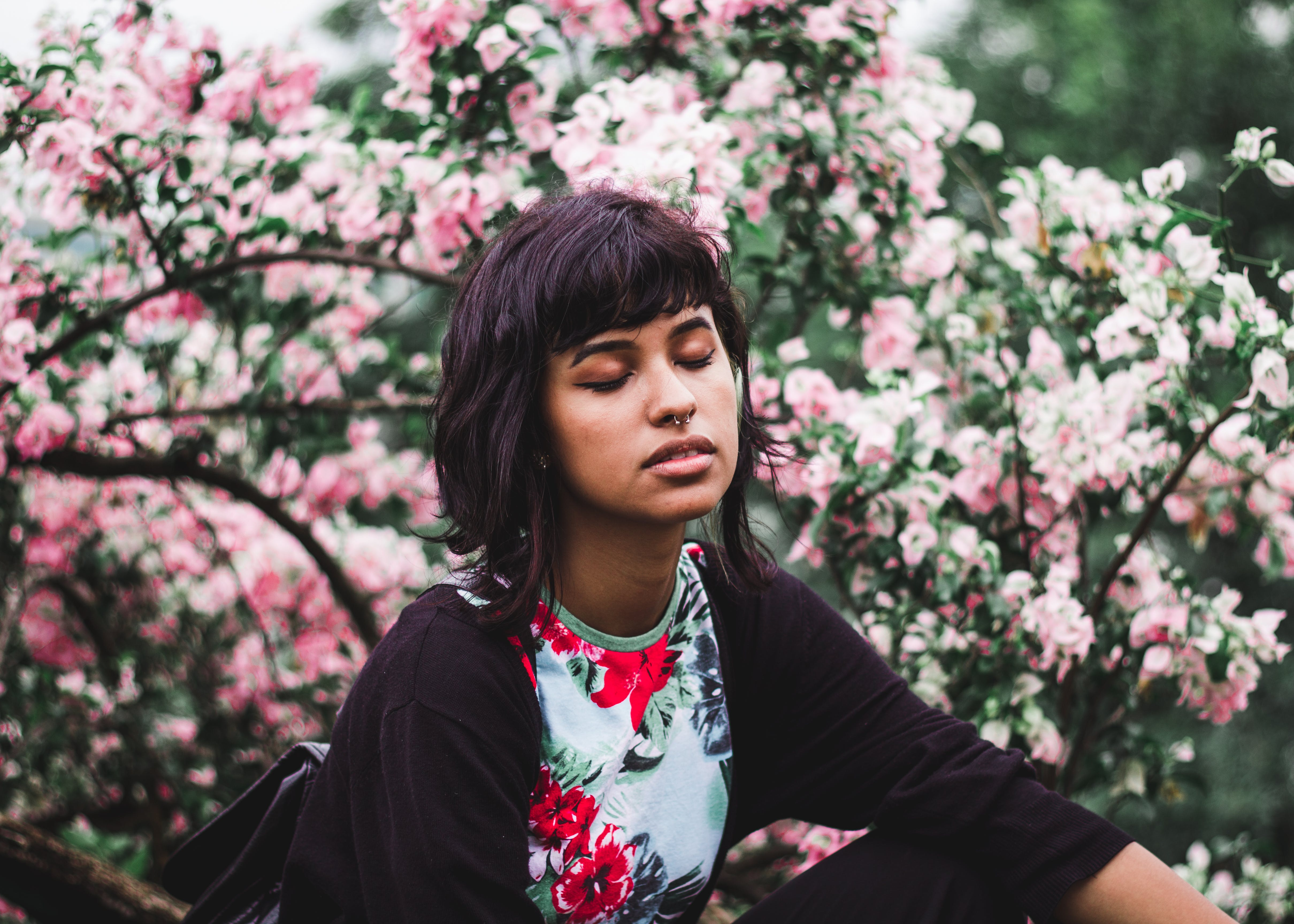 Woman Wearing White and Red Floral Crew-neck Shirt Near Pink Petaled Plant