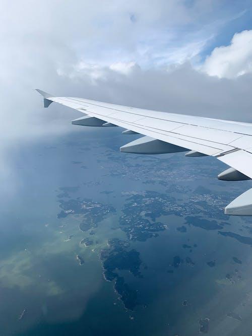 白い雲の上の白い飛行機の翼