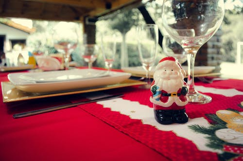Santa Claus Ceramic Figurine Next to Wine Glasses and White Ceramic Plate