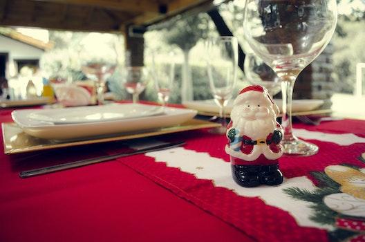 Santa Claus Ceramic Figurine Next to Wine Glasses and White Ceramic Plate