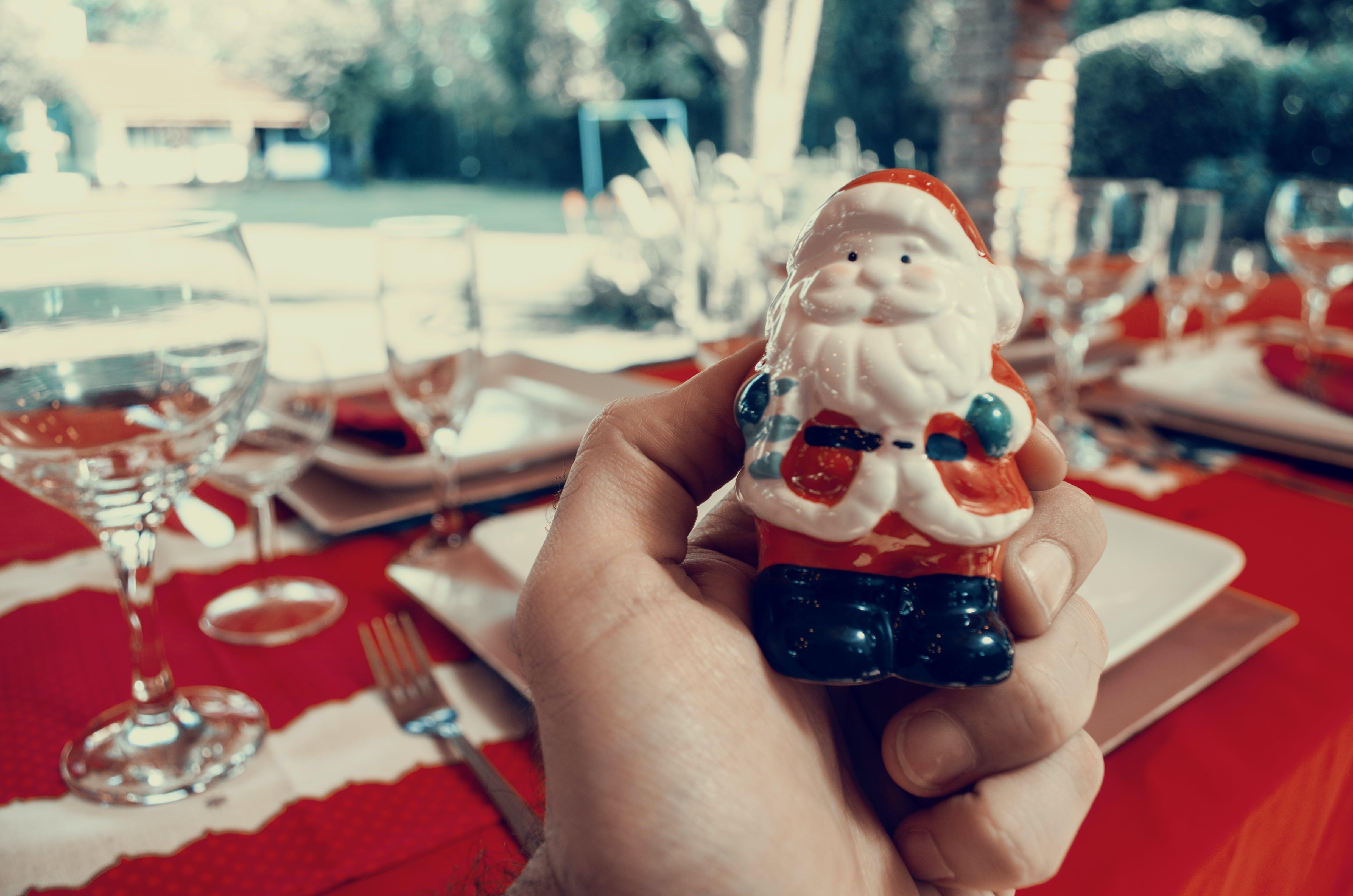 Person Holding Santa Claus Figurine