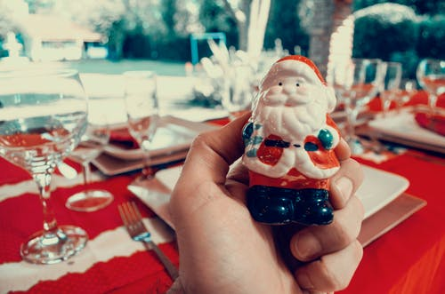Person Holding Santa Claus Figurine
