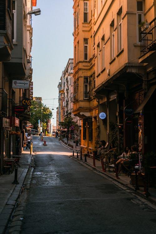 People on the Sidewalk of a Street Between Buildings