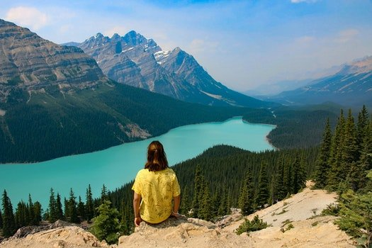 Person Sitting on Rocky Mountain Near Body of Water