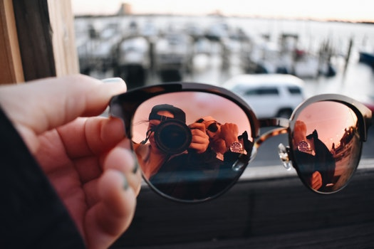 Close-Up Photography of a Person Holding Sunglasses