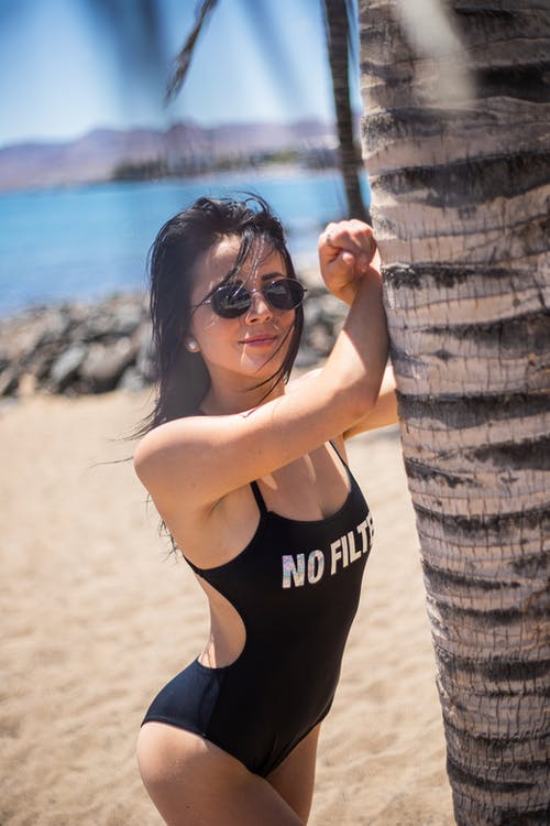 Woman in Black and White Bikini Leaning on Brown Wooden Post