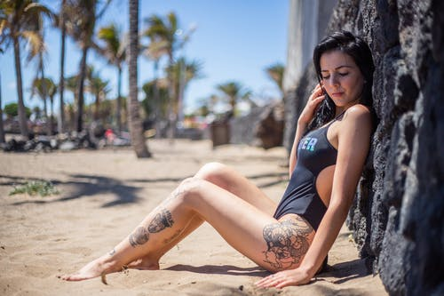 Woman in Blue Tank Top and Blue Denim Shorts Sitting on Brown Sand