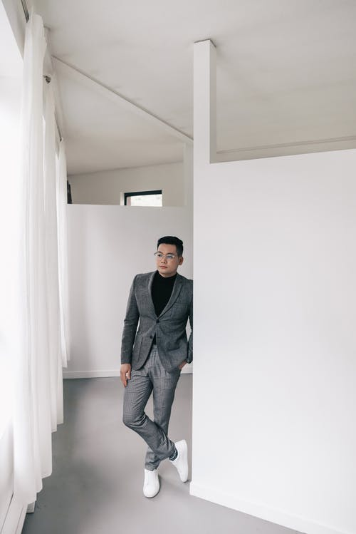 A Man in Suit Standing Beside a Wall