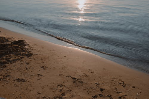 Brown Sand Near Body of Water during Sunset