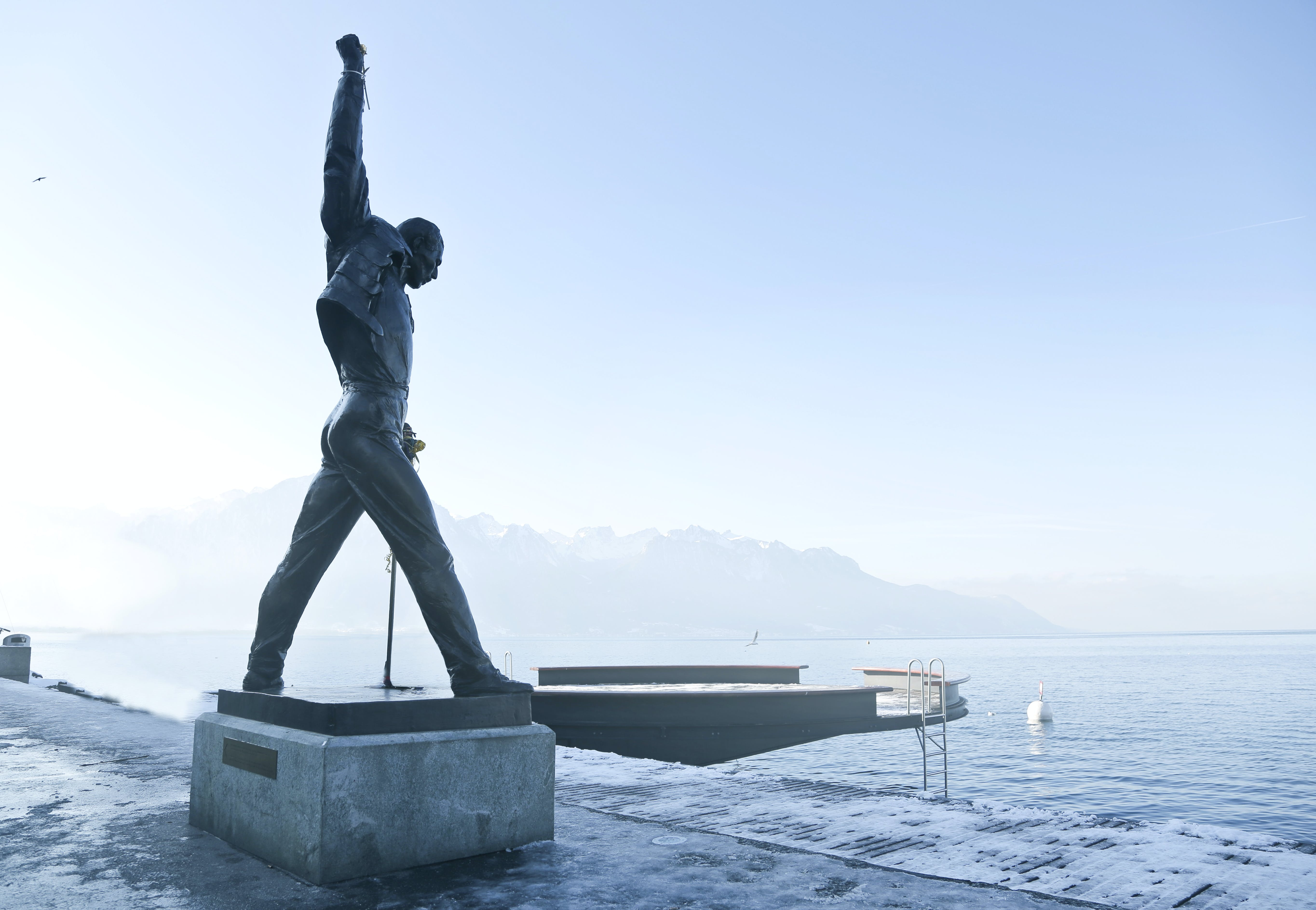 Gray Metal Statue of Man Raising Hand Near Dock
