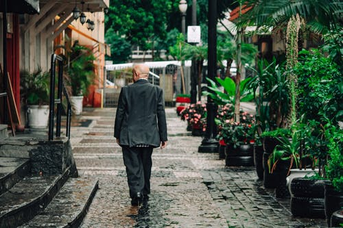 Man in Black Suit Standing on Sidewalk