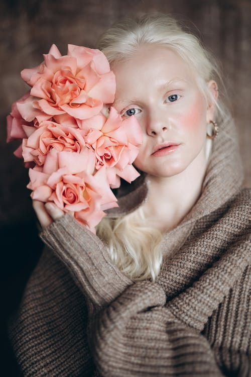 Woman in Gray Knit Sweater Holding Pink Rose