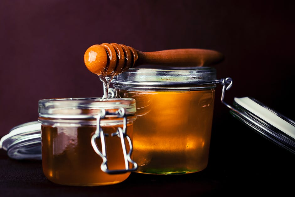 two jars of honey and a honey comb