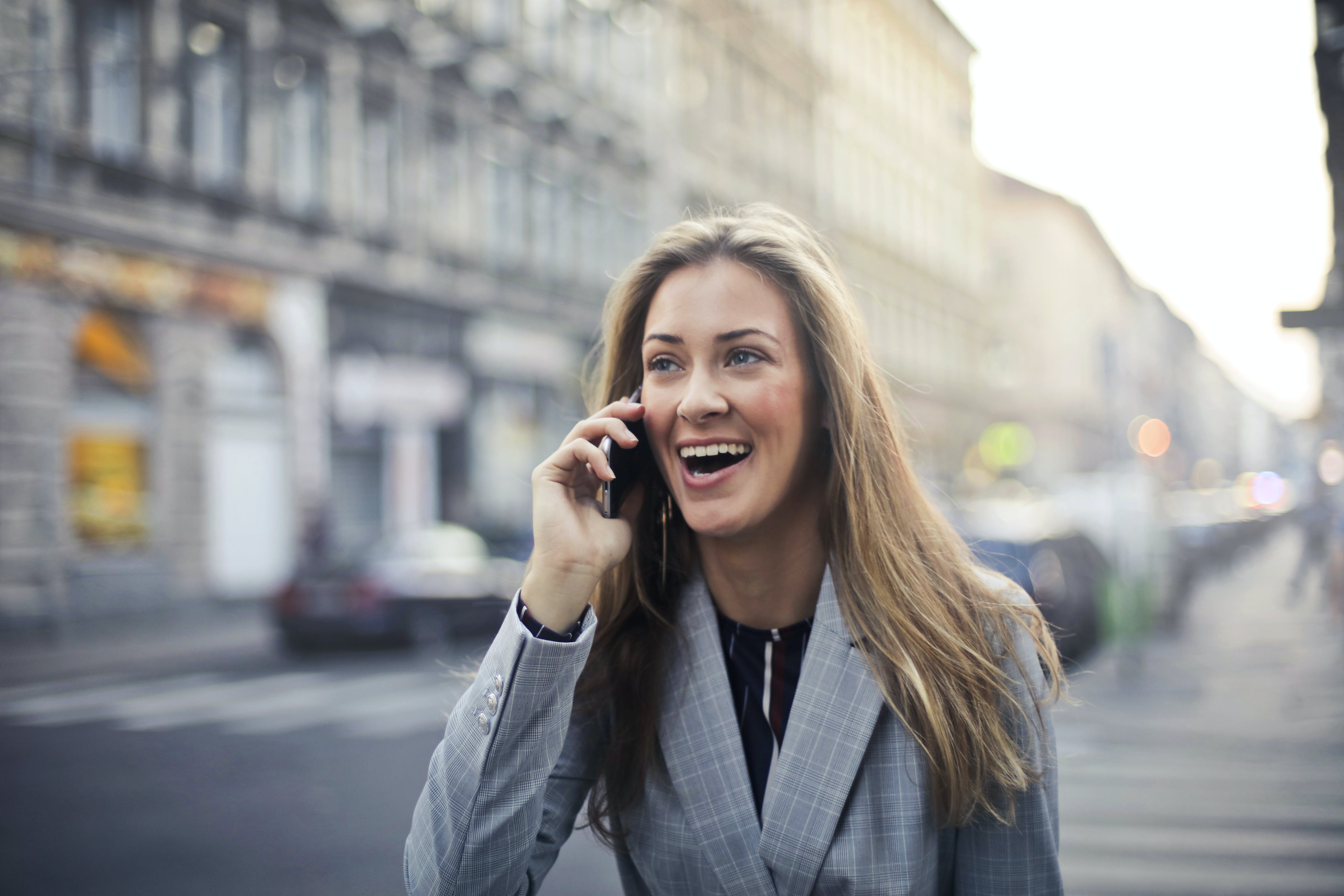 Blonde Hair Woman Wearing Gray Suit Jacket Holding Smartphone
