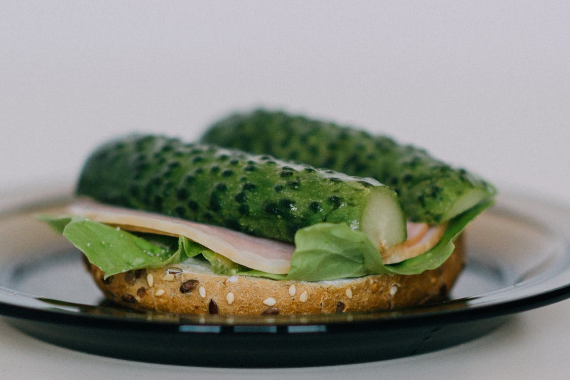 Selective Focus Photography of Bread With Zucchini on Round Glass Plate